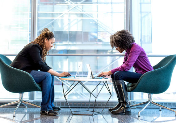 two WOC type on laptops