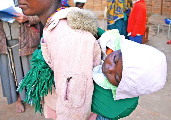 woman in Tanzania carries baby on back