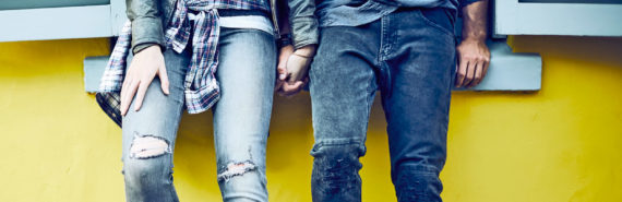 couple leans on yellow wall
