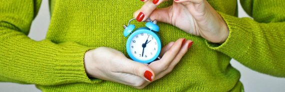 woman in green sweater holds clock