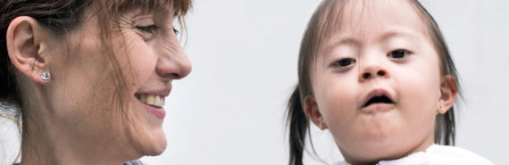 woman smiles at girl with Down syndrome