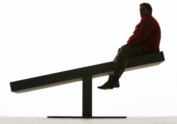 overweight man on a seesaw