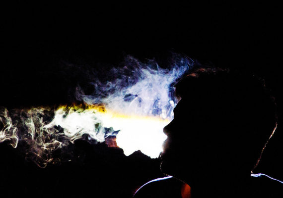 man's face in silhouette with smoke