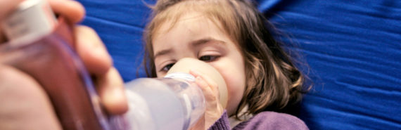 little girl uses inhaler