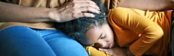 girl sleeps on mom's lap