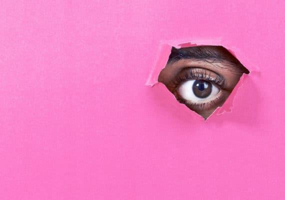 eye looks through pink paper