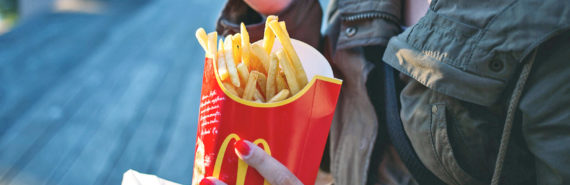 woman eats fast food french fries