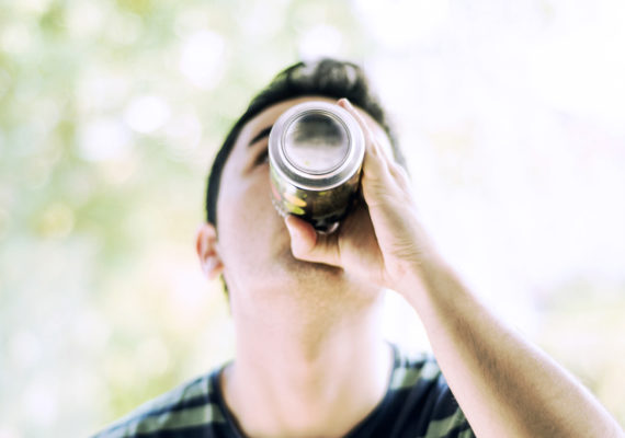man drinks from a can