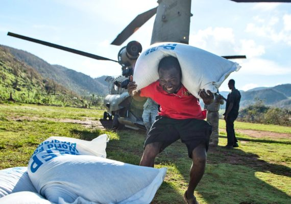 A citizen of Beaumont, Haiti unloads a bag of rice from a CH-47 Chinook on October 13, 2016. (Credit: Tech. Sgt. Russ Scalf/USAF via The 621st Contingency Response Wing/Flickr)