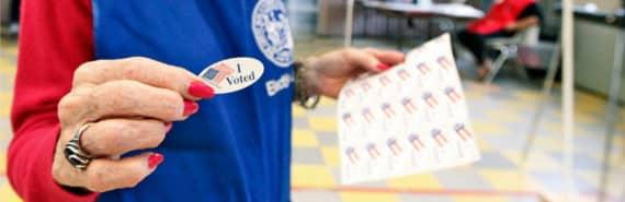 polling volunteer gives I voted sticker