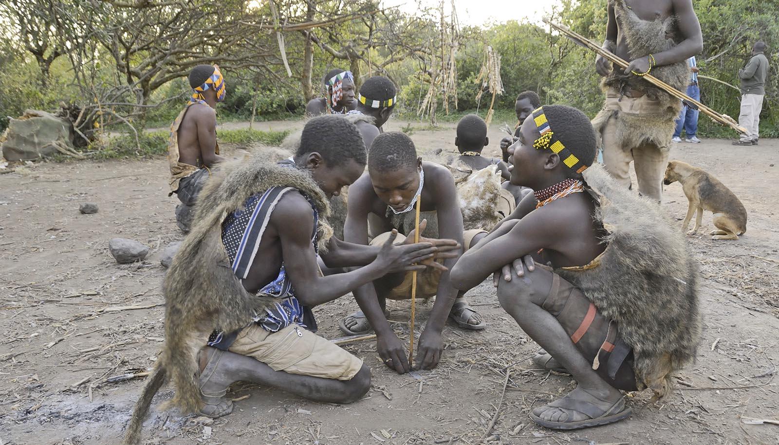 Hadza boys build a fire