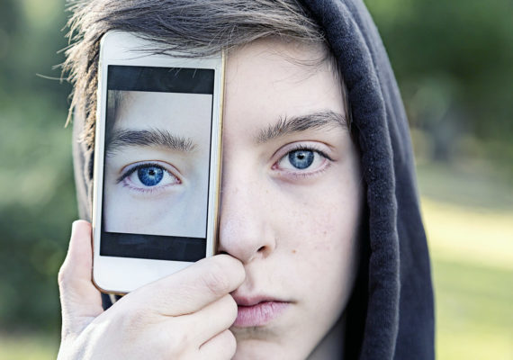 teen holds a phone over one eye