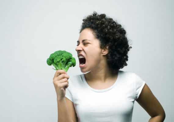 woman eats broccoli