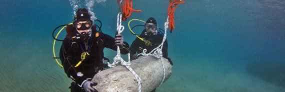scuba divers remove a column drum from the harbor front area.