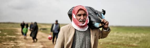 refugees walk land in syria