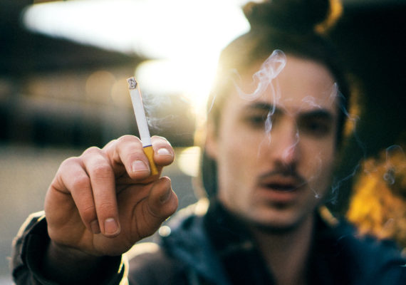man holds up cigarette