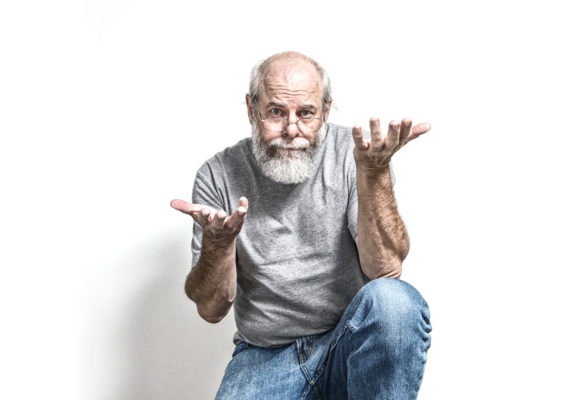man kneels while shrugging