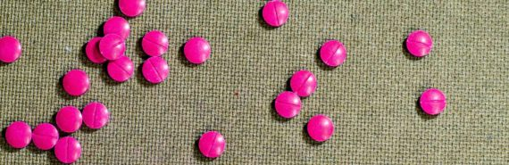 pink pills on wood