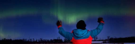 person gestures at aurora borealis