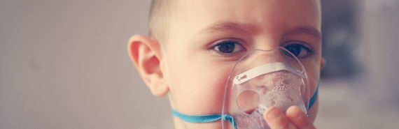 little boy uses a nebulizer