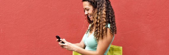 woman uses phone against red wall