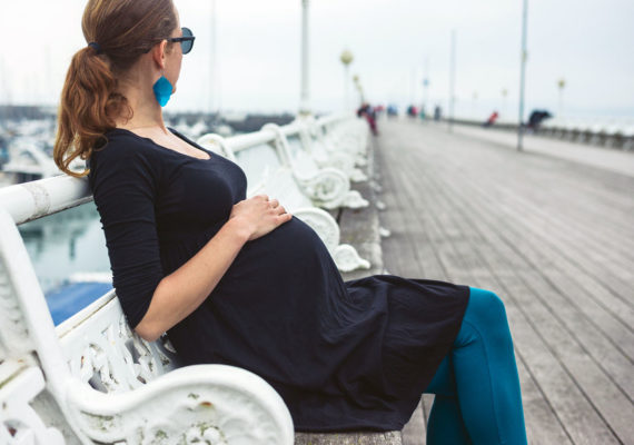 pregnant woman sits on a bench on a pier