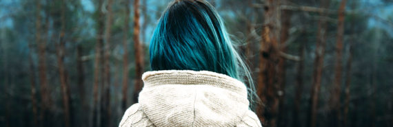 woman with blue hair looks into forest