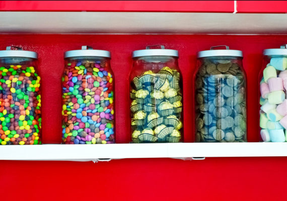 jars of candy against red wall
