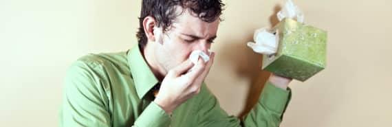 man blows his nose