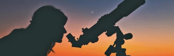 woman looks through telescope