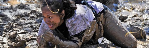 woman crawls in mud at tough mudder