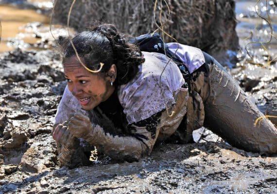 woman crawls in mud at tough mudder