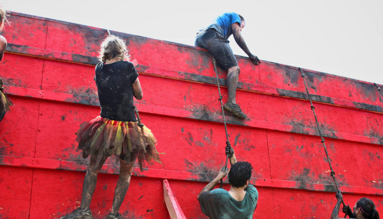 people scale wall during tough mudder
