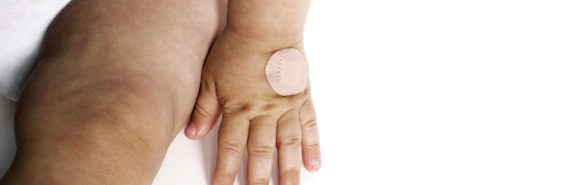baby's hand with bandaid on white