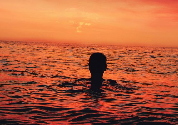 boy floating in ocean at sunset