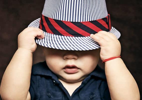 baby boy pulls down hat