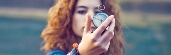 woman holds up compass