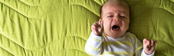 baby cries on green bedspread