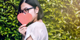 woman holds heart over face