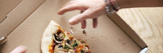 man grabs last slice of pizza