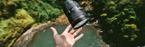 hand catches long lens over waterfall