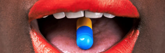 red lipstick and pill on tongue