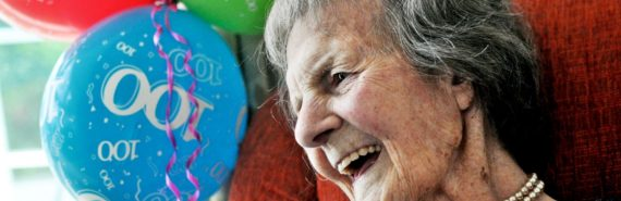 woman with 100th birthday balloons