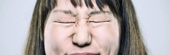 woman scrunching her eyes shut