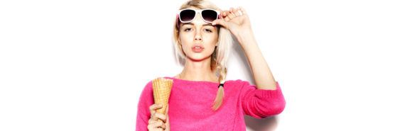 woman in pink eats ice cream cone