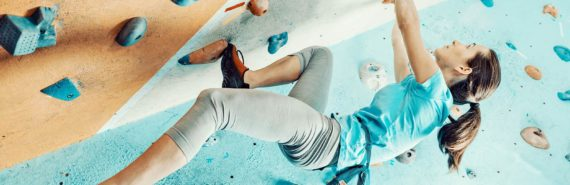 bouldering woman hanging from wall