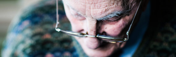 elderly man looks down through glasses
