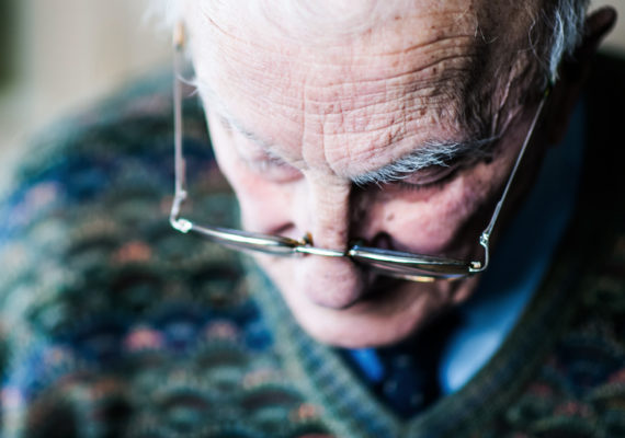 elderly man looks down through glasses