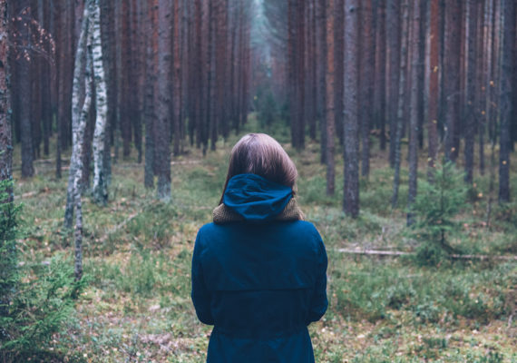woman stands in a forest