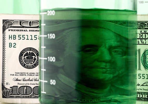 beaker of green liquid and money